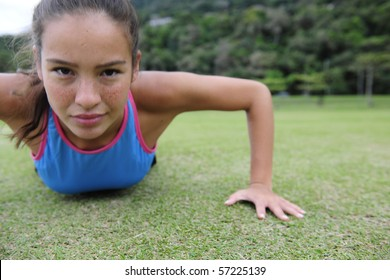 attractive, sporty woman doing push-ups outdoors in the park