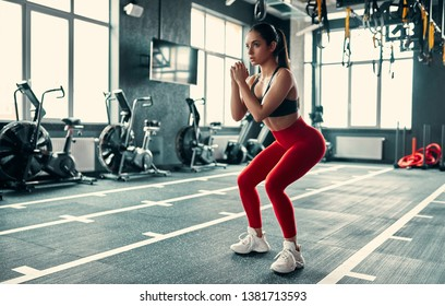 Attractive sporty woman in gym. Young perfect shaped brunette doing squats
