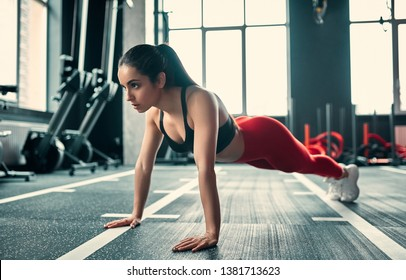 Attractive sporty woman in gym. Young perfect shaped brunette doing plank. Push-ups