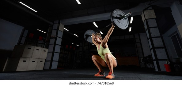 Attractive sporty woman performing overhead squats with a heavy barbell at the gym complex crossfit overhead performance athlete active lifestyle weightlifting bodybuilder