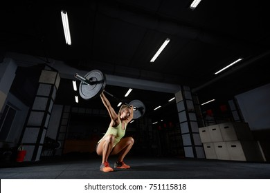 Attractive sporty woman performing overhead squats with a heavy barbell at the gym complex crossfit overhead performance athlete active lifestyle weightlifting bodybuilder. Crossfit style, deadlift
