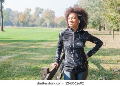 Attractive Sporty Woman Relax After Training Listening Music At Park, Leaning On Wooden Fence In Nature And Looking At Side