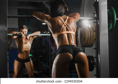 Attractive sporty woman relaxing with barbell in gym. Beautiful fitness girl resting after sport workout exercises. Rear view of female in sportswear with perfect body posing in the gym.