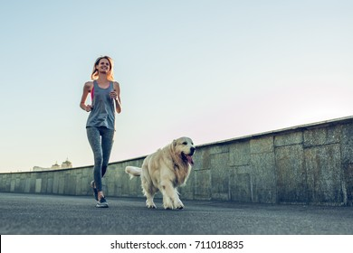 Attractive sporty woman is running in the city with dog golden retriever.