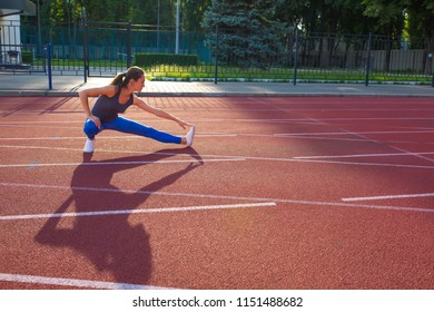 Attractive sporty woman stretching before race at the stadium, empty space