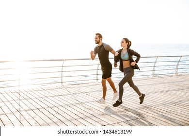 Attractive sporty young fitness couple wearing sportswear jogging together at the beach