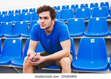 Attractive sporty young man model in blue shirt relaxing on blue stadium seats after training staring into camera