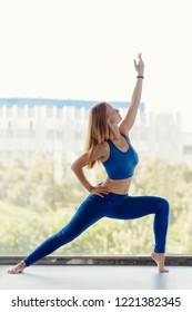 Attractive sporty young woman practicing yoga near window