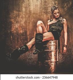 Attractive steampunk girl sitting on barrel