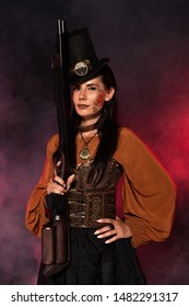 attractive steampunk woman holding gun and standing with hand on hip in pink smoke
