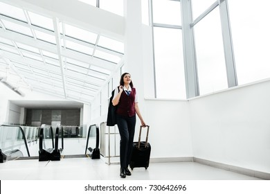 Attractive stewardess comes with travel suitcase