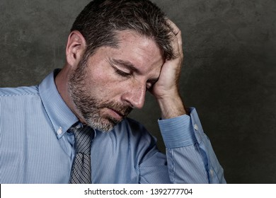 Attractive and stressed businessman in shirt and necktie suffering depression problem feeling tired and overwhelmed isolated on grunge background in company business stress and overwork