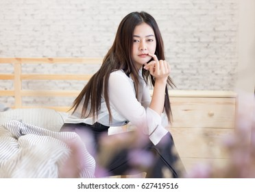 Attractive and strikingly business woman wearing sexy uniform sitting down on the bed while thinking something and she looking to the camera with lonely emotional
