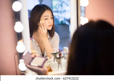 Attractive and strikingly woman make up herself in front of the mirror at the vanity (dressing table) and her eyes looking herself in the mirror while she puff the powder on her cheek