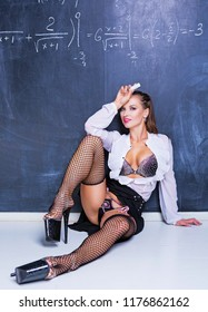 attractive striptease dancer dressed as teacher against a chalkboard in the classroom