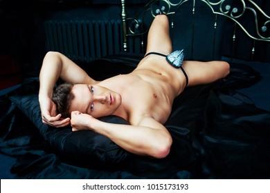 attractive striptease dancer  wearing underwear in bed with black linen