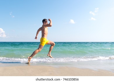 Attractive strong athlete running fast along the sea