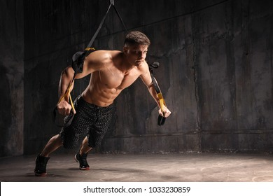 Attractive strong man does crossfit push ups with Trx fitness straps