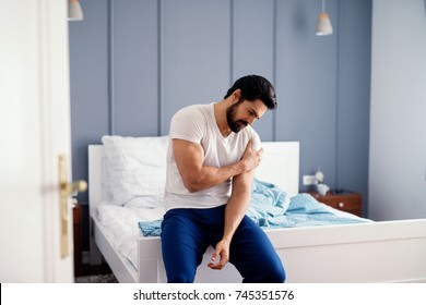 Attractive strong man sitting on the bed and holding painful shoulder with another hand.