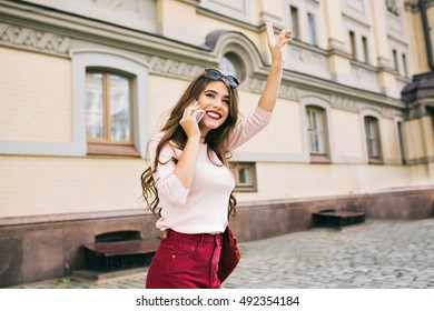 Attractive student girl with long hairstyle is walking in the city. She is speaking on phone and gratulates somebody.