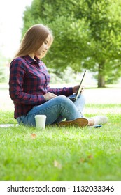 Attractive student girl sitting with a laptop in a summer park
