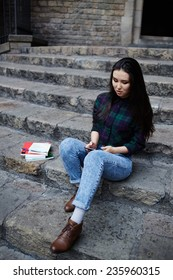 Attractive student girl using a smart phone sitting on the steps outdoors, asian race student girl browsing the internet with her cell phone during class break at university school, technology concept