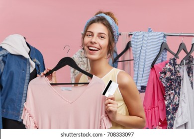 Attractive student girl wearing headband holding discount card while shopping, feeling happy, refreshing her wardrobe. Cute woman about to try on stylish pink top in dressing room of clothing store