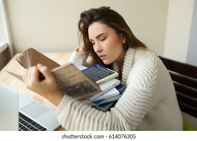 Attractive student sleeping with a book at the desk. Girl tired of studying and doing her homework. Bored reading a book