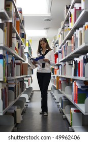 Attractive student standing in between bookshelves in modern university library reading a book.