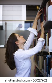 Attractive student standing in front of a bookshelf in modern university library reaching for a book.