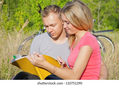 Attractive students studying together in the park