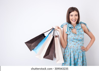 Attractive styled girl is standing and posing. She is holding a lot of packets of bought things. The lady is smiling and looking at the camera happily. Isolated and copy space in left side