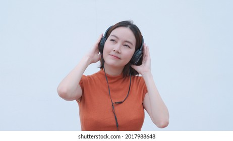 attractive stylish asian woman listening music in headset on white background. closeup portrait happy female relaxing playing song playlist via headphone. entertainment technology smiling. half length