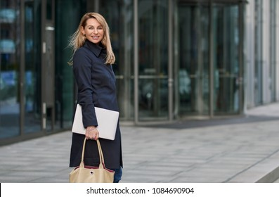 Attractive stylish blond businesswoman walking through town pausing to look back at the camera with a warm friendly smile in front of an office block entrance