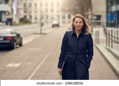Attractive stylish blond woman leaving her workplace as she walks down a quiet high key urban street smiling as she carries her laptop with copy space