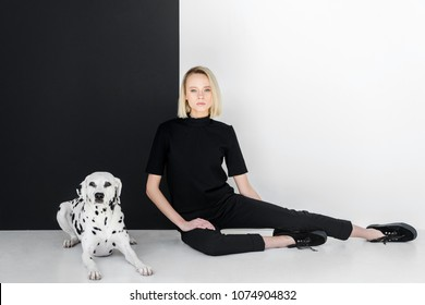 attractive stylish blonde woman in black clothes sitting near black and white wall with dalmatian dog