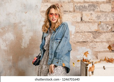 attractive stylish blonde woman in jeans oversize jacket walking against wall in street, autumn spring fashion trend