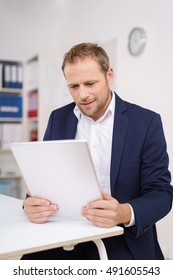 Attractive stylish businessman reading a handheld document as he sits at a table in the office