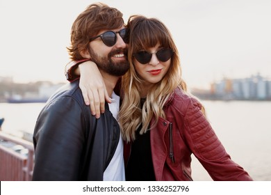 Attractive stylish couple in love posing outdoor, hugging and walking on quay. Soft evening colors. Fashionable look. Trendy sunglasses. Man and woman embarrassing.