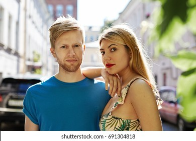Attractive stylish couple of young Caucasian tourists posing on street and looking at camera while sightseeing in old European city on summer sunny day; blurred building and cars in background