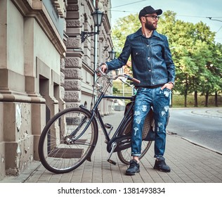 Attractive stylish hipster posing next to his bicycle near building. He is holding his bicycle. Man is wearing denim, cap and glasses. One hand he put to his pocket.