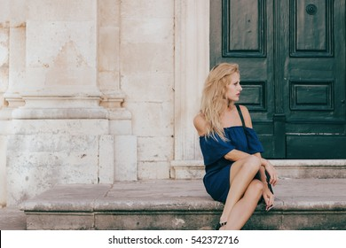 Attractive stylish hipster woman sitting on the old entrance stairs and posing for a photo at Dubrovnik old town, Croatia