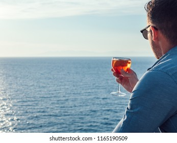 Attractive, stylish man in sunglasses, holding a glass of beautiful pink cocktail on an open deck of a cruise ship on a background of sunset, sea waves and clear sky. Concept of sea travel and recreat