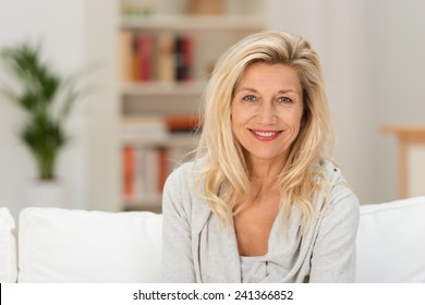 Attractive stylish middle-aged blond woman sitting on a sofa in her living room smiling at the camera, head and shoulders portrait