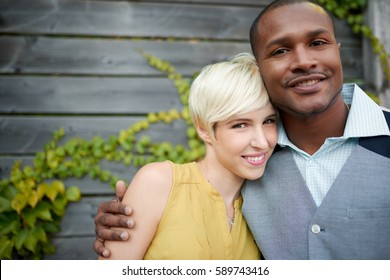 Attractive and stylish multicultural couple in love cuddling by a fence in an ivy-filled urban setting
