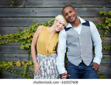 Attractive and stylish multicultural couple in love holding hands by a fence in an ivy-filled urban setting