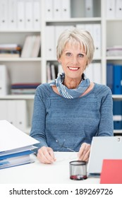 Attractive stylish senior manageress sitting in her office surrounded by business files and paperwork smiling at the camera