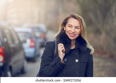 Attractive stylish smiling blond woman in a misty street in winter wearing a warm overcoat and handbag over her shoulder standing glancing to the side