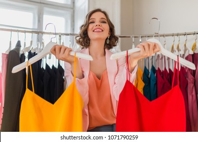 attractive stylish smiling woman choosing apparel in clothing store, elegant style, spring summer fashion trend, colorful dresses, shopaholic, fashionista, happy, exited, deversity