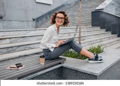attractive stylish smiling woman in glasses working typing on laptop, freelancer sitting in park on stairs drinking coffee, urban city street style, business center, online education